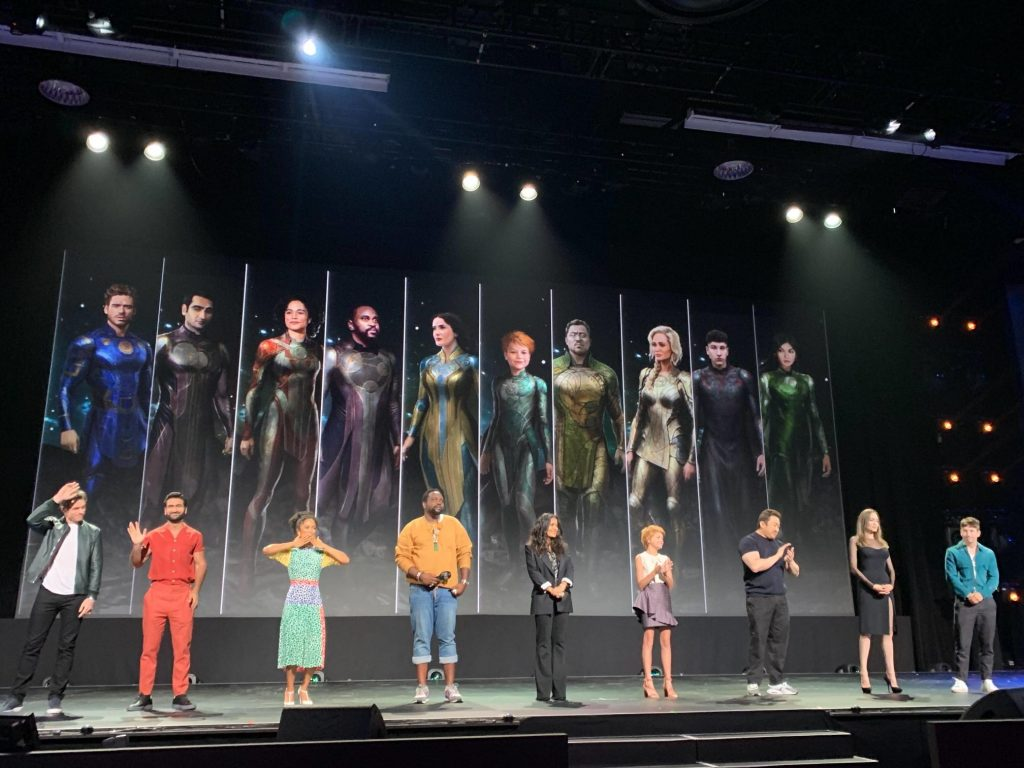 The cast of The Eternals standing on stage at D23 in front of artwork of them in costume.