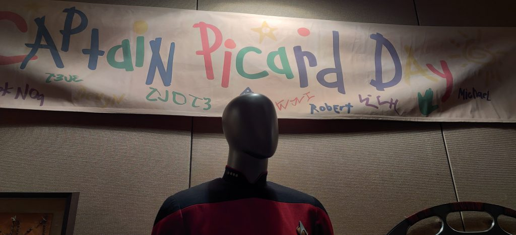 Picard's uniform from Star Trek: The Next Generation below the Captain Picard Day banner.
